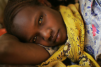 Fatima,  14 year old  darfurian refugee, waits for her nephew to go through medical treatment in the Oure Cassoni UNHCR refugee camp in Chad on Jan 02 2005. More than 20000 refugees live in the camp. Fatima lost her entire family during an attack on her village perpetuated by military forces of the Government of Sudan in 2004. since she moved to Chad where her uncle is taking care of her and her sister's son which is now under the care of doctors in a camp medical facility.