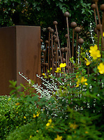 An open boundary fence of allium heads and a wall both made of mild steel that has rusted over time