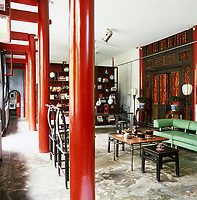 Industrial structural pillars in the main living room have been painted in red lacquer and the carved screen was originally plastered over