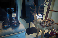 Switzerland. Canton Ticino. Lugano. Shop window with sale banners. A pair of plastic rainy boots and a stuffed deer, both items with reduced tags prices. 1.01.2020  © 2020 Didier Ruef