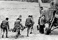 The body of one of the victims of what appears to be a tit-for-tat double murder between Castleblaney, Co Monaghan, Rep of Ireland, and Newtownhamilton, Co Armagh, N Ireland, 25th August 1975, is carried to British Army helicopter. Colm McCartney, 22 years, Drumarg Park, Armagh, and John Farmer, 32 years, Dungannon Road, Moy, Co Tyrone, both Roman Catholics, were murdered by UVF members posing as a military patrol. The incident occured less than a month after the Miami Showband incident. One of the bodies was found in the laneway of a house owned by the relative of a Protestant found shot dead 3 miles away only a week earlier. McCartney & Farmer were returning from an all-Ireland GAA semi-final. 197508250609.<br /> <br /> Copyright Image from Victor Patterson,<br /> 54 Dorchester Park, Belfast, UK, BT9 6RJ<br /> <br /> t1: +44 28 90661296<br /> t2: +44 28 90022446<br /> m: +44 7802 353836<br /> <br /> e1: victorpatterson@me.com<br /> e2: victorpatterson@gmail.com<br /> <br /> For my Terms and Conditions of Use go to<br /> www.victorpatterson.com