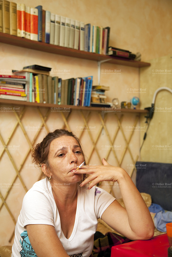 Italy. Lazio region. Capena. Cornelia Mihaelu is a romanian citizen and has lived in Italy for the last 10 years. She smokes a cigarette and sits on a couch in her flat's living room. Capena (until 1933 called Leprignano) is a town and comune in the province of Rome. 24.09.2011 © 2011 Didier Ruef