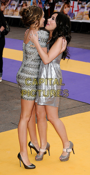 "MILEY CYRUS & DEMI LOVATO.UK Premiere of ""Hannah Montana: The Movie"" at the Odeon Leicester Square, London, England..April 23rd 2009 .full length silver shiny strapless dress  grey gray shoes mary janes open toe creased platforms silver beaded beads embellished jewel encrusted shoulder pads structured shoulders sculpted shoes profile hug embrace funny gesture mouth open metallic.CAP/CAN.©Can Nguyen/Capital Pictures."