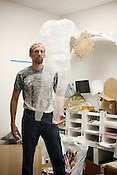 Mark Plaga surrounded by his creations, including a packing tape sculpture of his son, inside the Durham TechShop.