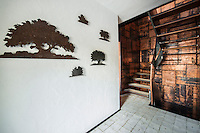 Metal cut outs of trees displayed on a bright white wall lead up to the dramatic copper clad staircase by Giancarlo Candeago