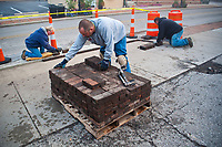 Westerville city workers reinstall bricks along the sidewalk on West Main Street to complete a curb replacement project. The old curbs were cracked and broken and the bricks were removed while the new concrete was poured and set.
