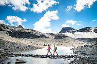 Two women crossing a stone trail through a small lake while on the Via Valais, a multi-day trail running tour connecting Verbier with Zermatt, Switzerland.
