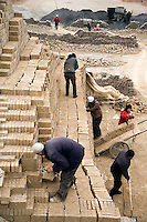 Workers carry loads of freshly-made bricks at a brickyard in Linxia, Gansu, China.