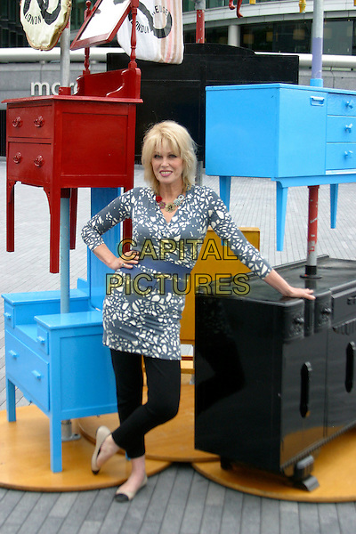 JOANNA LUMLEY .The launch of the old furniture recycling scheme, The Scoop, More London, the Queen's Walk, London, England. .July 12th, 2010 .full length black grey gray white print top blue waist belt trousers leggings hand on hip chest of drawers dresser .CAP/JEZ.©JEZ/Capital Pictures.