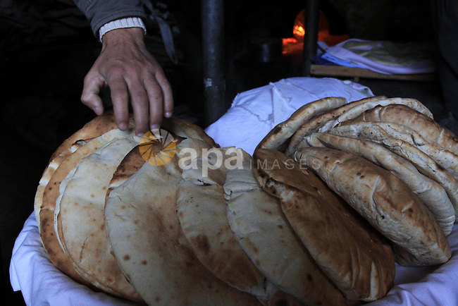 A Palestinian worker bakes bread inside his bakery in Gaza City on Dec 19,2009. Photo by Mohammed Asad