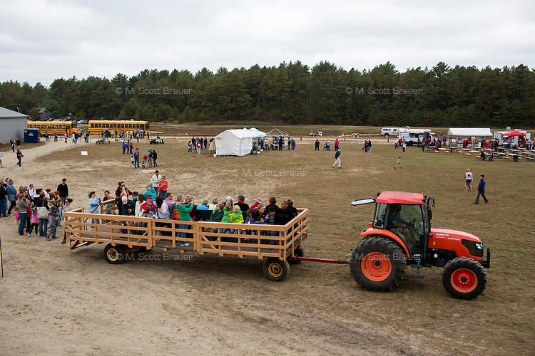 A cranberry farmer talks about cranberry farming as a tractor pulls people along on a bog tour during the AD Makepeace Company's 10th Annual Cranberry Harvest Celebration in Wareham, Massachusetts, USA. AD Makepeace is the world's largest producer of cranberries. These cranberries, wet harvested with varied colors, are destined for processing into juice, flavoring, canned goods and other processed foods.