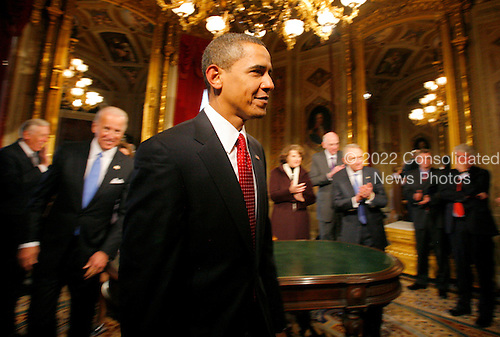 Washington, DC - January 20, 2009 -- United States President Barack Obama leaves the President's Room as he is applauded by members of the Joint Congressional Committee on Inaugural Ceremonies (JCCIC), after signing his first act as president, a proclamation, moments after being sworn in as the 44th President of the United States during the inaugural ceremony in Washington, Tuesday, January 20, 2009.  .Credit: Molly Riley - Pool via CNP