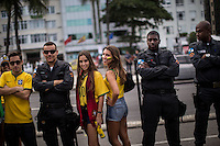 Rio de Janeiro, Brazil.Footbal fans together with police officers.Dozens of demonstrators gathered today in Copacabana, the tourist district of Rio de Janeiro, to protest against the World Cup, while hundreds of fans witnessed on the beach, a few meters, todays opening game of the tournament.