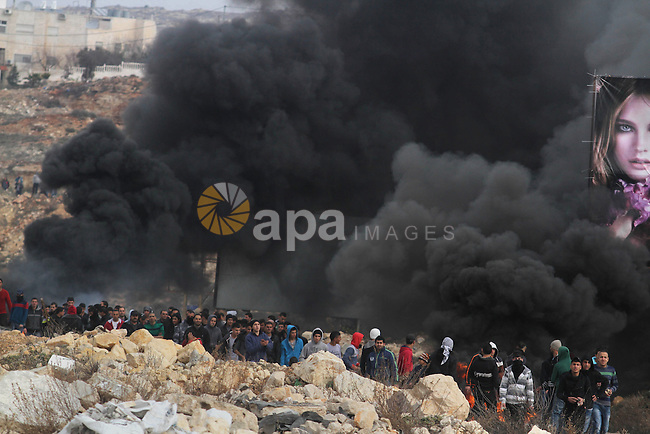Youth from the Palestinian refugee camp of al-Jalazoun, clash with Palestinian police as they block the main road leading to the West Bank city of Ramallah  January 12, 2014. At least 50 people were hurt on Sunday in a clash between Palestinian police and residents of the refugee camp protesting against a strike in a U.N. aid agency that has paralysed services, police and an ambulance service said. The demonstration was the most violent in a series of protests stemming from a strike for higher pay by local employees of the United Nations Relief and Works Agency (UNRWA). Photo by Issam Rimawi