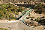 Green painted double-arch truss bridge carries a country road over the Arroyo Seco wash in the Salinas Valley.