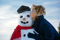 Deutschland, Bayern, Chiemgau: junge Frau umarmt einen Schneemann | Germany, Bavaria, Chiemgau region: young woman embraces a snowman