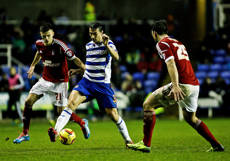 Reading's Stephen Kelly sheilds the ball from Nottingham Forest's Jamie Paterson (l) and Nottingham Forest's Jack Hobbs (r)<br /> <br /> Photo by James Marsh/CameraSport<br /> <br /> Football - The Football League Sky Bet Championship - Reading v Nottingham Forest - Wednesday 1st january 2014 - Madejski stadium - Reading<br /> <br /> &copy; CameraSport - 43 Linden Ave. Countesthorpe. Leicester. England. LE8 5PG - Tel: +44 (0) 116 277 4147 - admin@camerasport.com - www.camerasport.com