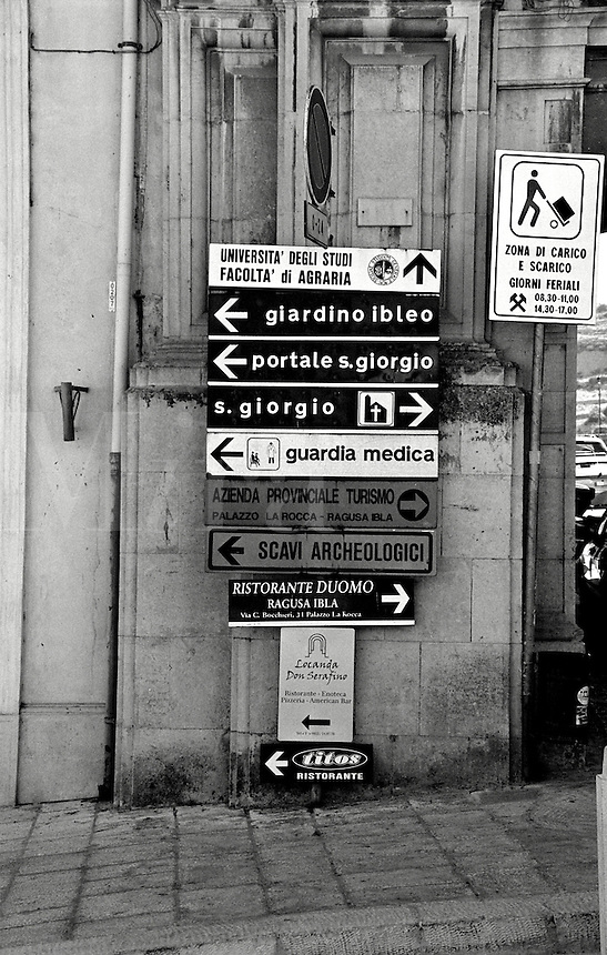 Signs pointing the way to various tourist attractions and near the Cathedral San Giorgio in Ragusa, Sicily, Italy