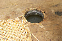 Oak barrique barrel with fermenting white wine, bung hole covered with jute. Detail of the bung hole and the wine inside Chateau Belingard Bergerac Dordogne France