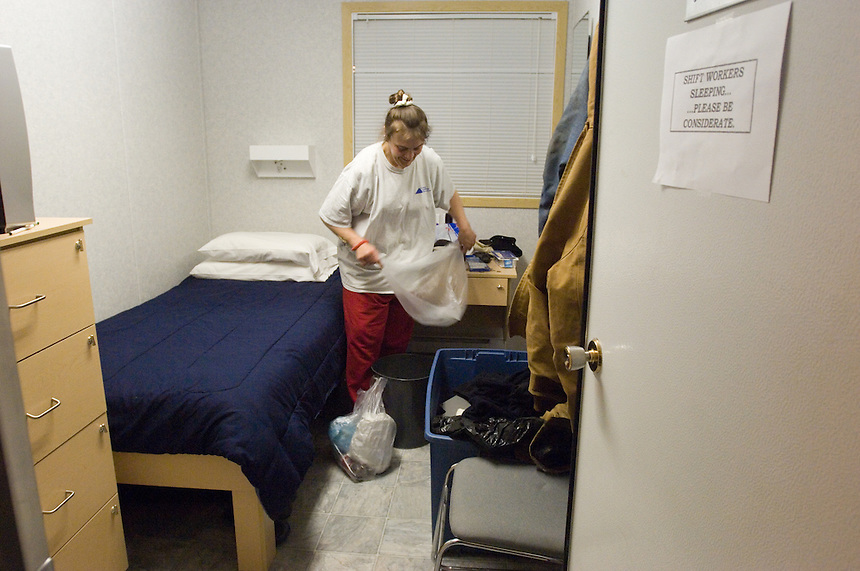 Housekeeper Debra Hoffeditz empties trash in a dormitory room at a man camp that houses Halliburton employess some 20 miles south of Pinedale, Wyo., Thursday, March 2, 2006. (Kevin Moloney for the New York Times)