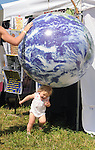 A toddler has a ball with a large Globe along the Midway at the Falcon Ridge Folk Festival, held on Dodd's Farm in Hillsdale, NY on Saturday, August 1, 2015. Photo by Jim Peppler. Copyright Jim Peppler 2015.
