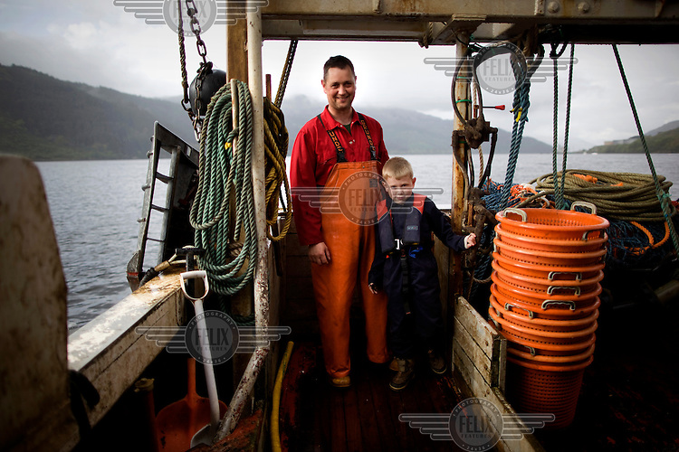 Fisherman Peter Campbell stands with his 7 year old son Gregor on a boat on the River Clyde. The Campbell family have been langoustine fishermen for three generations on the river and surrounding sea lochs.