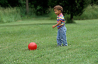 Boy playing with red ball on lawn