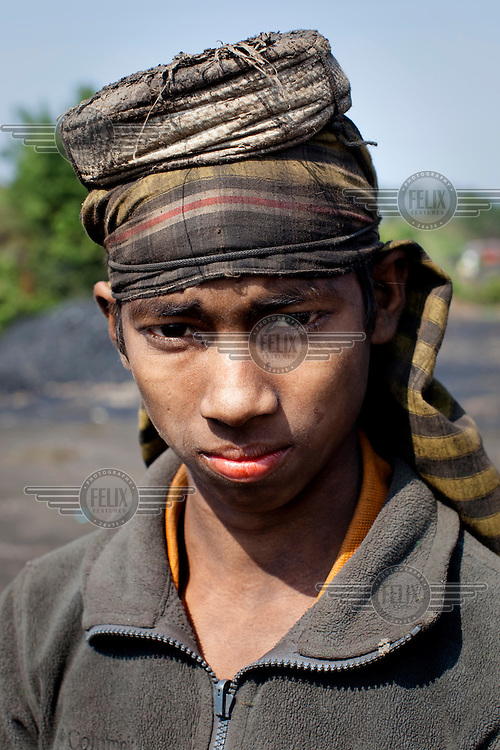 12 year old Abdul Kayum (scarf) at the Kong Ong Depot, the largest coal storage depot in the Jaintia Hills. The coal comes from privately owned mines in the surrounding region. There are approximately 5,000 privately owned coal mines in the region sitting on top of about 40 million tons of coal. Many use children, often trafficked, to work them under conditions that are hard and unregulated. The coal is dug out using primitive methods and basic tools.
