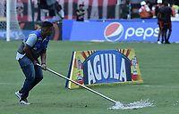 CALI - COLOMBIA, 21-04-2019: Un hombre barre el agua  acumulada después del aguacero previo al partido entre América de Cali y Millonarios por la fecha 17 de la Liga Águila II 2018 jugado en el estadio Pascual Guerrero de la ciudad de Cali. / A man cleans the rain water over the field prior the match for the date 17 as part of Aguila League I 2019 between America Cali and Millonarios played at Pascual Guerrero stadium in Cali. Photo: VizzorImage / Gabriel Aponte / Staff