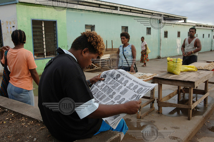 A man avidly reads a newspaper as market stalls are set up in the early morning. The Solomon Star has photographs of the fifty newly elected members of the Solomon Islands parliament. One hour later Snyder Rini resigned as Prime Minister. Rini had become PM just a week earlier, but his promotion had prompted mass protests because of corruption allegations.