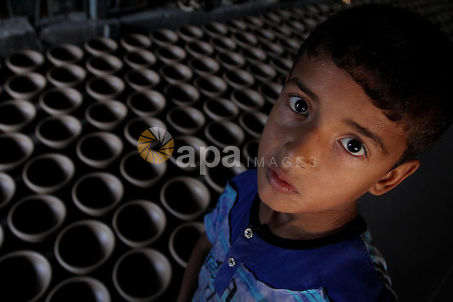 A Palestinian boy is standing next to the earthenware vases at a pottery workshop in Gaza City on Sept 2, 2010. Pottery is a very ancient and traditional industry in  Gaza City. Photo by Ashraf Amra