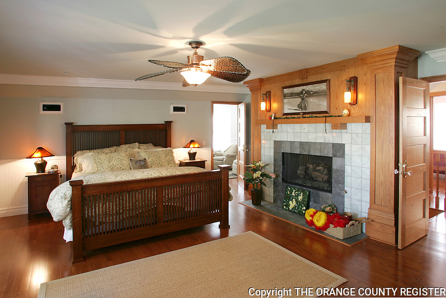 The upstairs master bedroom of this rebuilt Craftsman style house in Seal Beach features a large fireplace. The current owners rebuilt the original 1906 house from the ground up almost exactly like the original.