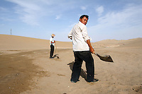 Two men trying to halt the encroaching sand. Desertification is the process by which fertile land becomes desert, typically as a result of drought, deforestation, or inappropriate agriculture. Dunhuang, Gansu Province. China