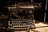 Underwood typewriter in corner of building in shadows and light with Crumbling Beach texture