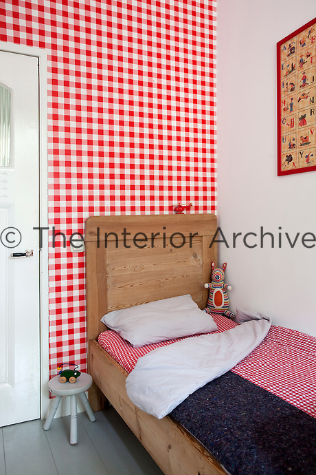 Each room has its own distinctive wallpaper. In Iris's son's bedroom, it's a bright red and white gingham pattern with matching bed linen