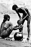 Migrant Labourer Family: Father and mother both join in giving their girl child a bath from a pot of water, on an empty stretch of a road in Mumbai where they are working as daily wage labourers on a road-morderninsing project. Photograph © Santosh Verma.