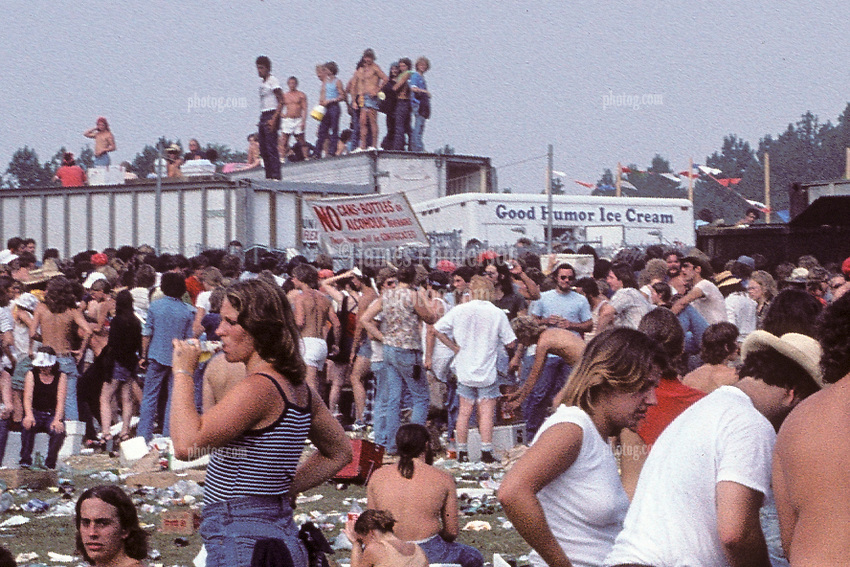 Folks going into The Grateful Dead Concert at Raceway Park; Englishtown NJ on 3 September 1977. Labor Day Weekend and on The Road into the Show. This shot taken outside the venue leading up to a gate which you can see here just to the left of center next to the Good Humor stand. Cropped tight of the gate area from the original format.