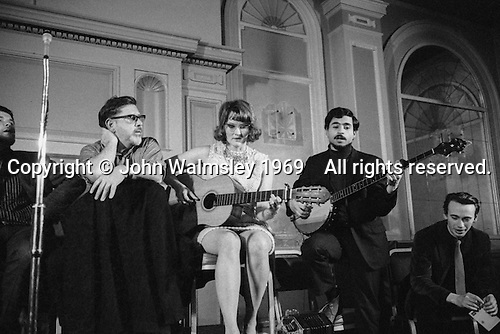 Ewan MacColl (on the left), singer, song writer, dramatist, playright, political activist (real name, Jimmie Miller) and Peggy Seeger, song writer and performer (and member of the North American Seeger folk family) at a folk club in London around the late 1960s.  If you can identify the venue, please let me know.