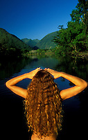 The back of a young woman with long flowing brown wavy hair at the stream that leads to the back of  Waipio Valley, North Kohala, Big island of Hawaii