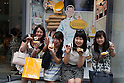Customers pose for the cameras outside the new pastry shop ''Dominique Ansel Bakery'' in Omotesando Hills on June 20, 2015, Tokyo, Japan. Japan is the first country outside the USA for the popular New York bakery to open a store. According to organizers, about 400 customers waited 3 to 4 hours in the morning to taste its original desserts such as the ''Cronut'' a croissant doughnut fusion creation by Chef Dominique Ansel. (Photo by Rodrigo Reyes Marin/AFLO)