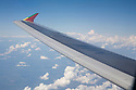 An airplane wing against clouds. The winglet (vertical portion at the end of the wing) is designed to increase fuel efficiency by reducing drag.