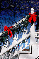 White railing decorated with evergreen boughs and red bows