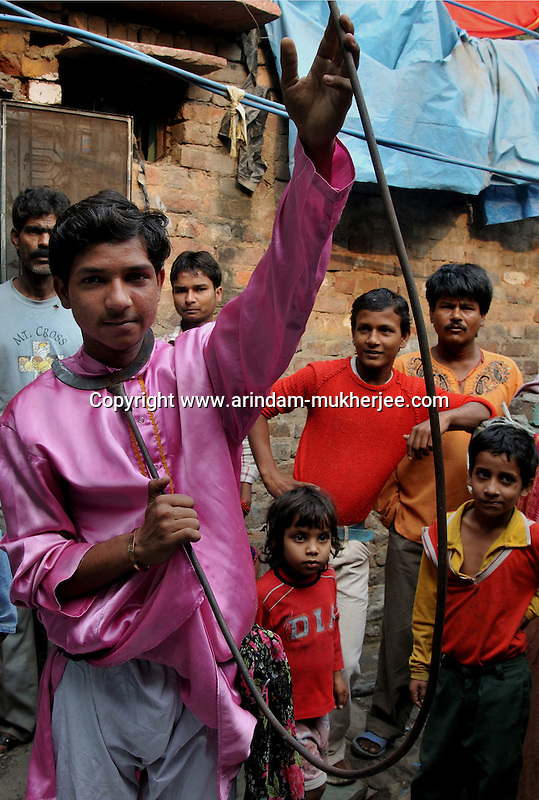 Shekhar a young boy of 14 year showing the iron rod after bending it with his neck at Katputly colony in New Delhi, India. 16.11.2009. Kathputly colony is a slum area in West Delhi. This slum seems like any other slum areas of modern India with dysfunctional electricity, non existing sanitation and poverty. As a part of Delhi, this is also ailed with water crisis. Large families live their lives crammed together in a single room with all the odds which complement poverty. One thing which differentiates this slum with any other is the people living in the colony. Nearly everybody in this slum is a traditional performing artist; and they have been migrating to this area for last 50 years from different parts of the country for a better livelihood. They are magicians, acrobats, jugglers, puppeteers, dancers and musicians. These artistes perform in star rated hotels, marriage ceremonies of the richer section, functions, and festivities all around the country and the world. Most of the artisans I met here, have performed in Europe and America but such opportunities are rare to come by. They struggle to keep their art form alive. They say that they don't get any help or support from the government for their basic needs and for the well being of the Kathputly colony -  though they have uphold the prestige of the country internationally. Polluted air, dirty alleys smelling of urine, colourful dress and sound of music characterise Kathputly colony, which is the one of its kind in India. Arindam Mukherjee