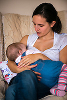 A woman in her early twenties breastfeeding her nine month old baby girl at home while sitting on a sofa in her living room. The mother is talking to and calming her baby.<br /> <br /> Image from the breastfeeding collection of the &quot;We Do It In Public&quot; documentary photography picture library project: <br />  www.breastfeedinginpublic.co.uk<br /> <br /> <br /> Dorset, England, UK<br /> 08/03/2013<br /> <br /> &copy; Paul Carter / wdiip.co.uk