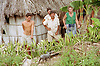 Farming family standing next to their wooden house with roof made from palm leaves on farm near Banes; Cuba,