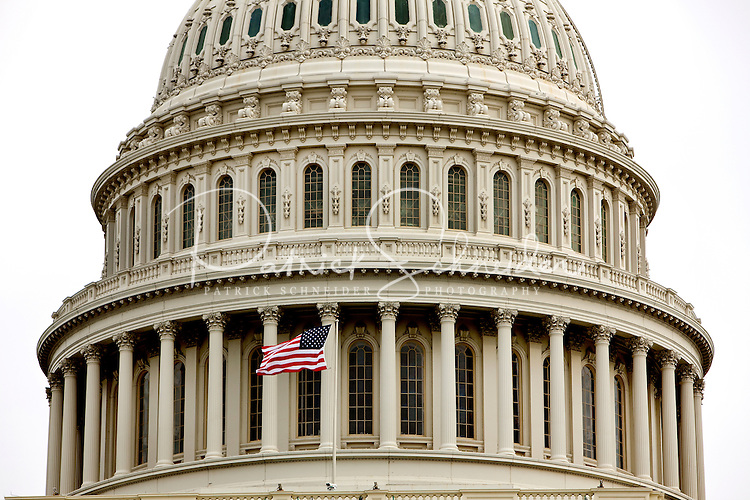 A United States flag flies in front of the US Capitol building in Washington, DC.