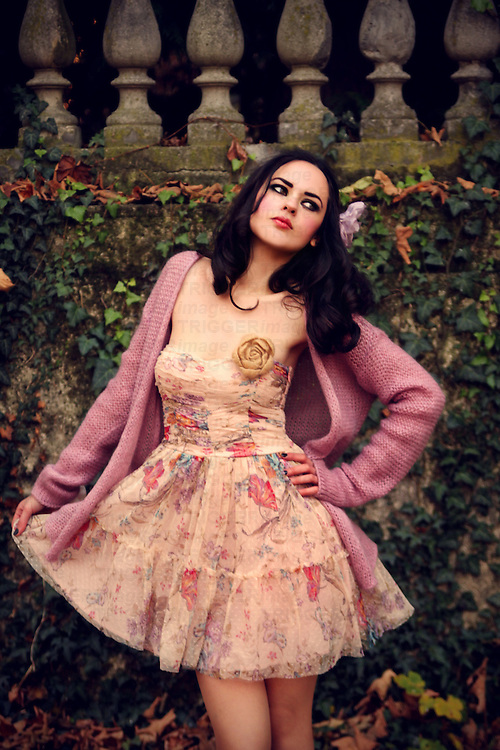 A pretty brunette with pale skin and dark hair in a  pastel floral dress and lilac sweater posing in a park.