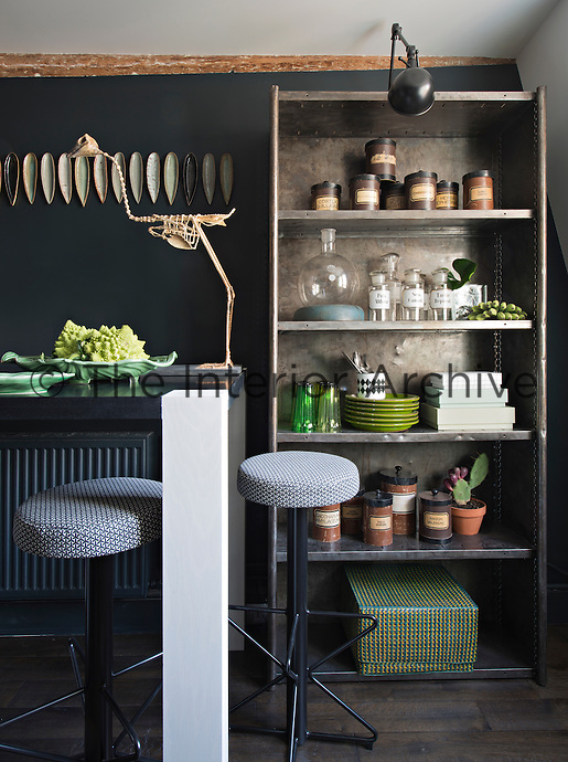 In the kitchen-diner, a bold colour approach of black and shades of grey is offset with items in varying shades of green. A breakfast bar with bar stools is situated to one side of the room providing a dining space. Storage jars and tableware are neatly arranged on a free-standing metal shelving unit.