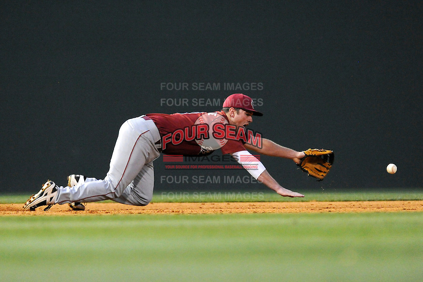 Third baseman Joey Pankake (9) of the South Carolina Gamecocks sticks his tongue out as he dives for a ground ball in a game against the Furman Paladins on Tuesday, April 8, 2014, at Fluor Field at the West End in Greenville, South Carolina. (Tom Priddy/Four Seam Images)