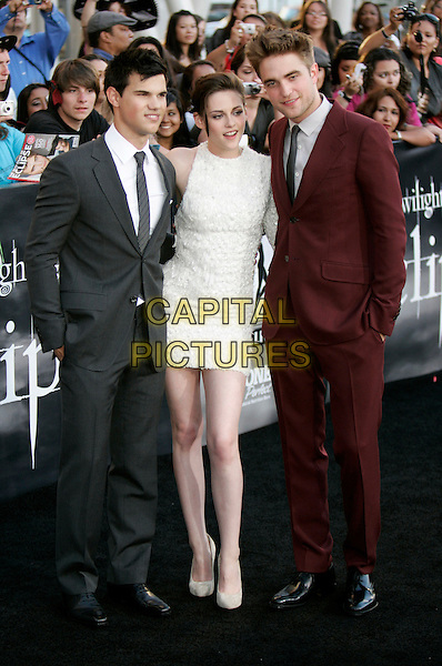 "TAYLOR LAUTNER, KRISTEN STEWART & ROBERT PATTINSON.at the World Premiere of ""The Twilight Saga: Eclipse"" held at the Los Angeles Film Festival at Nokia Live in Los Angeles, California, USA. .June 24th, 2010.arrivals full length cast red burgundy suit grey gray shirt tie maroon white dress .CAP/PE.©Peter Eden/Capital Pictures."